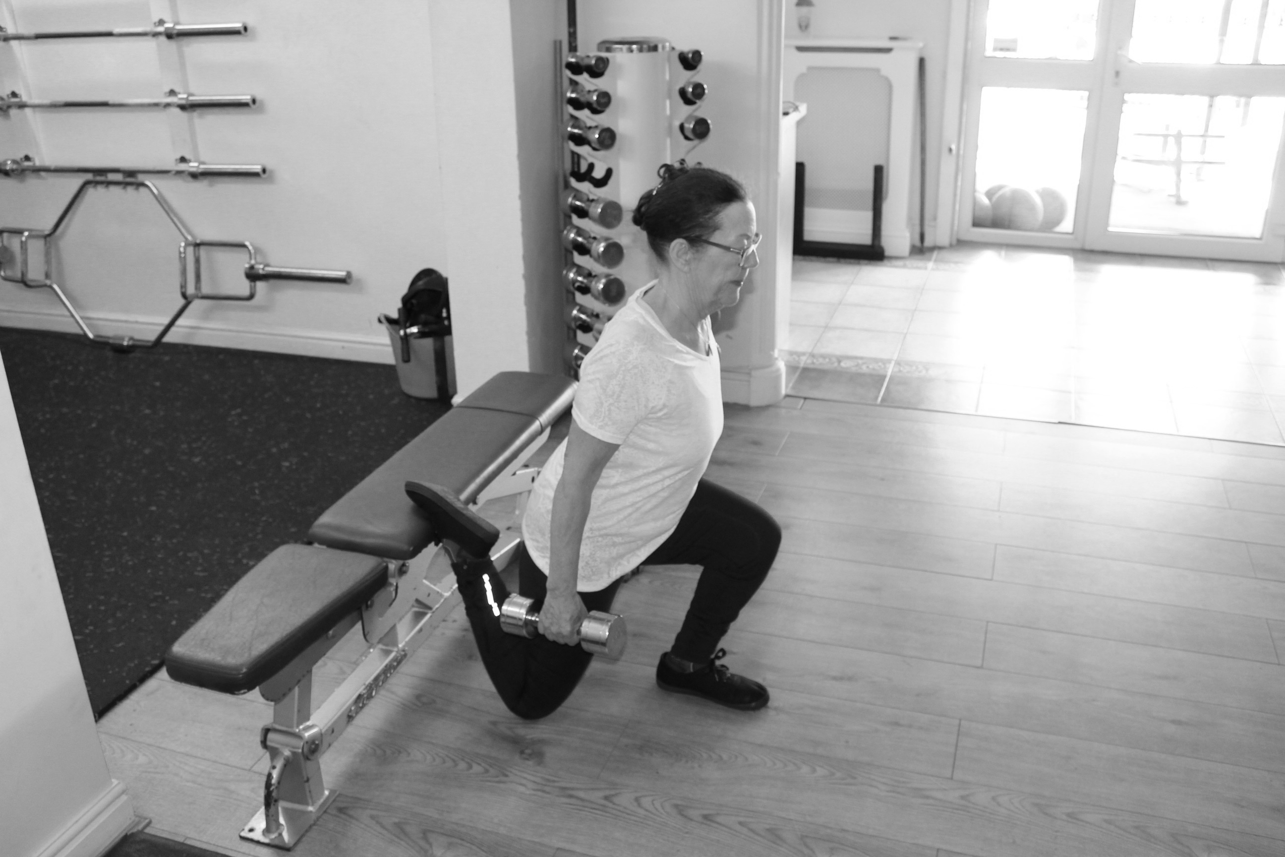picture of personal trainer with client on bench